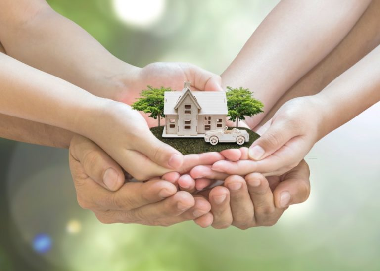 Safe family home model and garden on son daughter children kid guardian mother father hands, blur natural greenery tree planting environment background: Home loan property ownership assurance concept