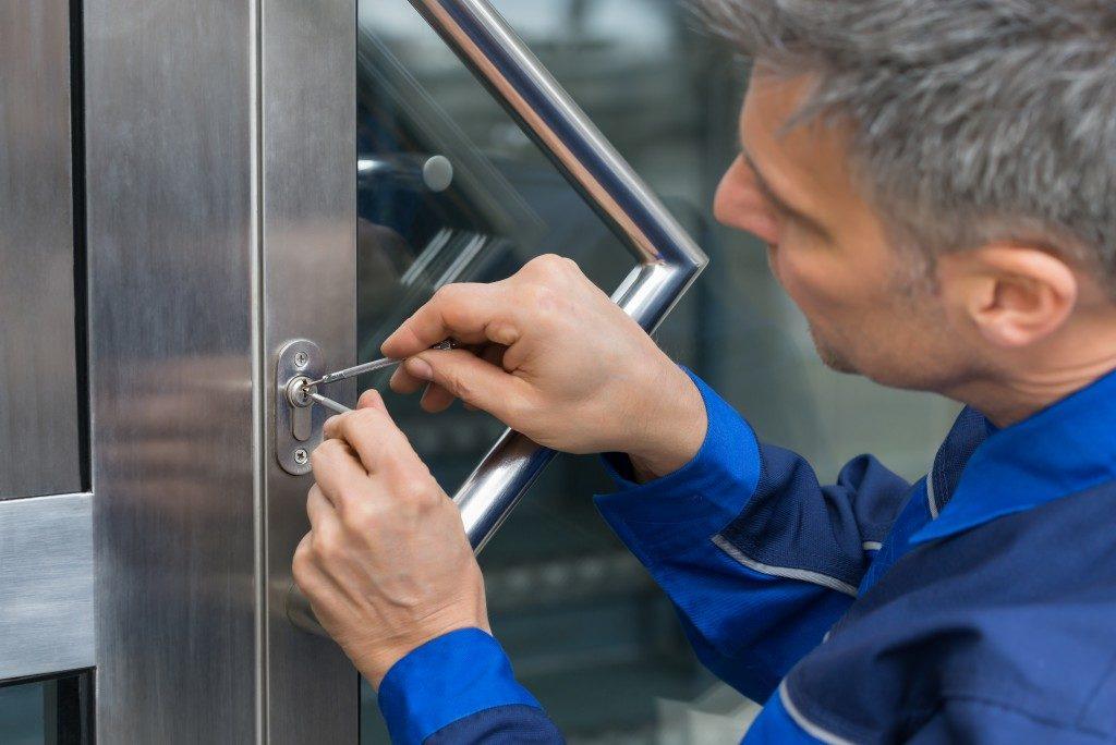 man picking lock of a house door