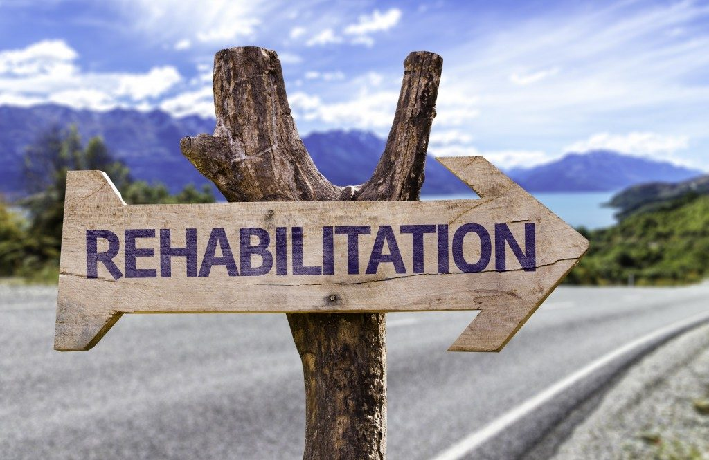 Rehabilitation wooden sign with a road background