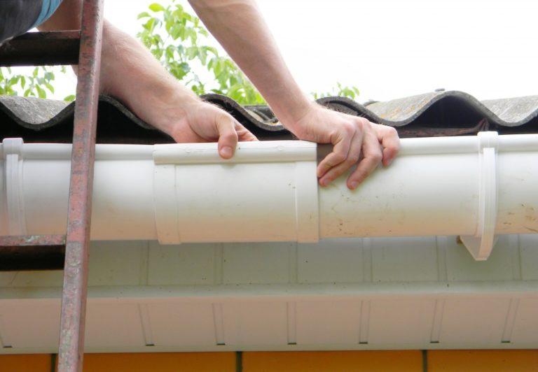 man installing a gutter system
