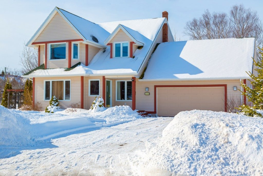 A family home in a north American suburb covered in snow.