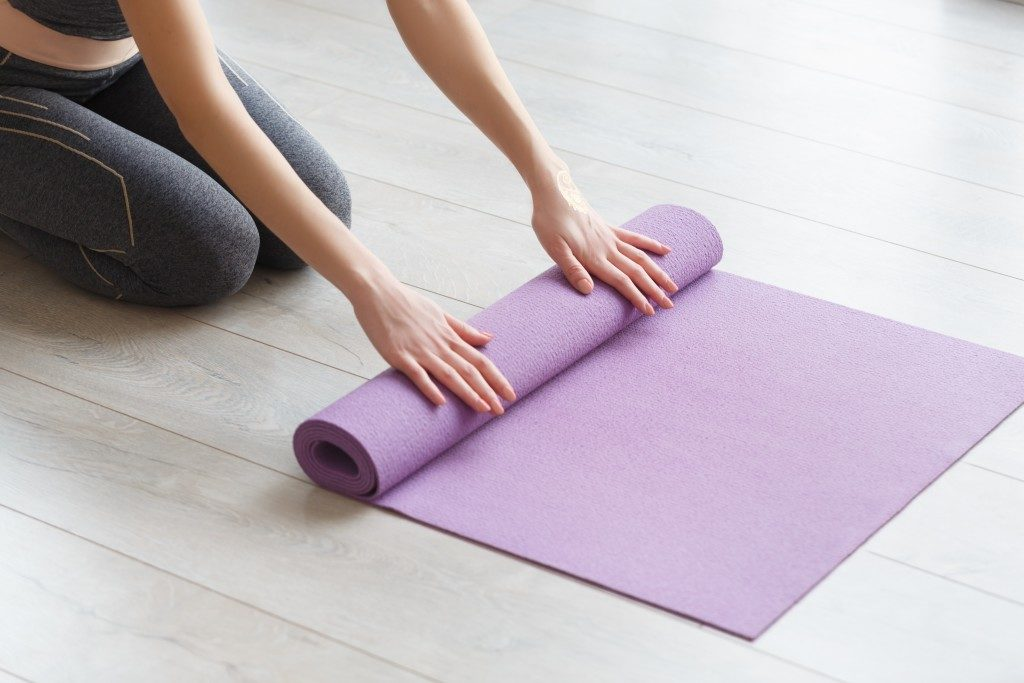 Woman rolling her lilac mat after a yoga class on wooden floor