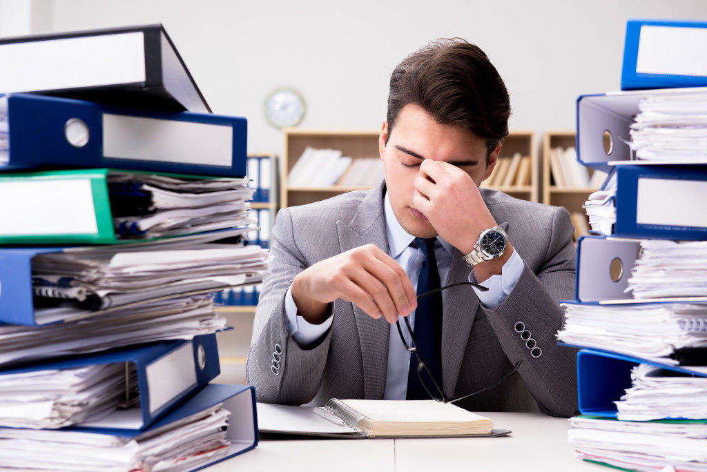 Stressed employee with piles of paperwork