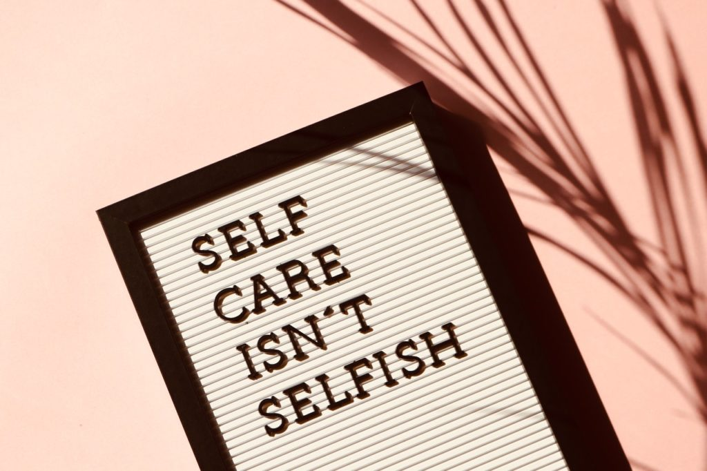 "sign that reads ""self care isn't selfish"""